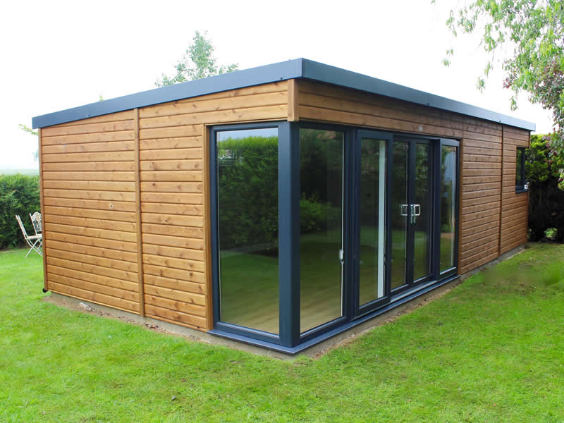 Large Manhattan Garden studio with horizontal cladding finished in light stain with glazed corner and sliding patio doors