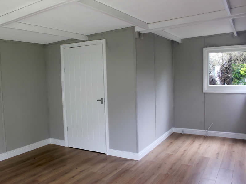 Internal view of a garden room showing light oak laminate flooring and pavilion grey painted walls.