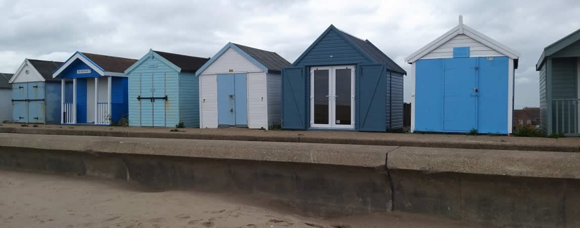 Beach Huts lined up in shades of blue