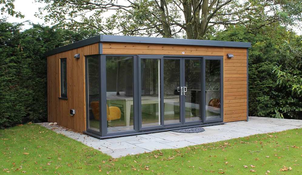Luxury garden room finished in stained vertical and horizontal redwood with sliding patio doors and a glazed corner