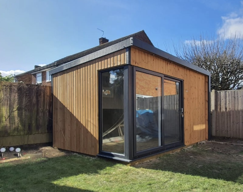 Contemporary Garden Room with glazed corner and sliding patio doors in vertical stained red wood 3mx4m