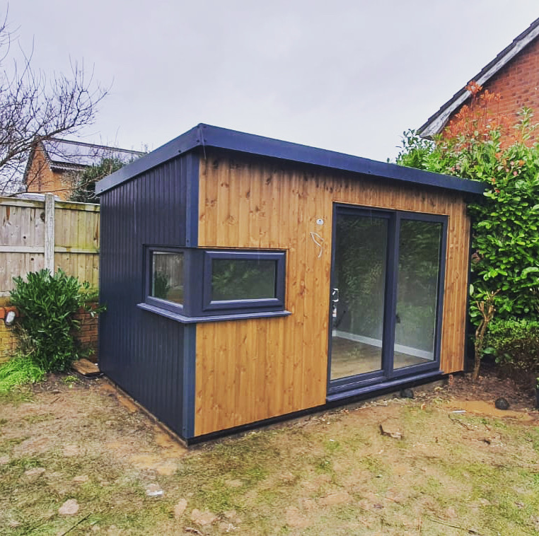 Garden Studio with pillar box side window ,front elevation vertical stained redwood, rear and side elevation vertical painted redwood in anthracite .