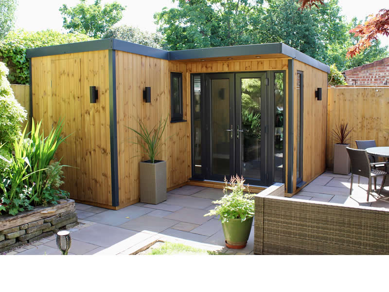 Pembroke L shaped garden room with secret door , vertical clad mid stain - by day