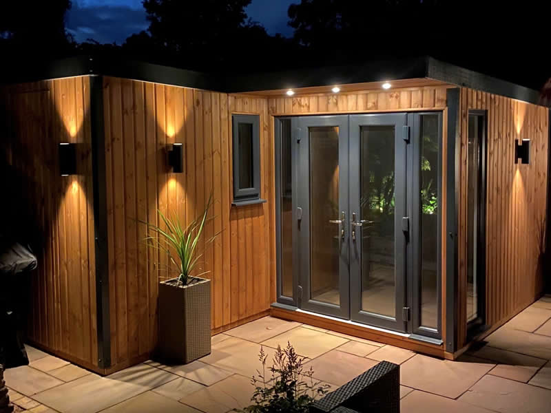 Pembroke L shaped garden room with secret door , vertical clad mid stain - by night